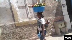 """""""Zungueira"""" com o filho nas costas"""