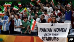 FILE - Fans cheer and wave the flag of Iran as Darya Safai (R) holds a large sign protesting the fact that women have not been allowed to attend volleyball matches in Iran.