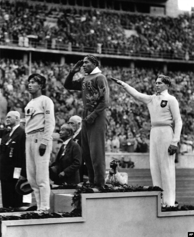 FILE - Jesse Owens, center, salutes during the presentation of his gold medal for the long jump, after defeating Nazi Germany's Lutz Long, right, during the 1936 Summer Olympics in Berlin.