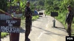 Personel Brimob melakukan penjagaan keamanan di Pos Sekat di desa Sedoa, Kecamatan Lore Utara, Kabupaten Poso, Sulawesi Tengah. (Foto: VOA/Yoanes).