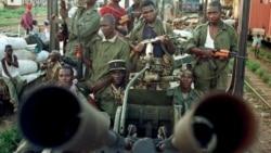 Basoda ba ba mbulamatari bazali kolakisa manduki na bango na Dolisie, 23 janvier 1999.