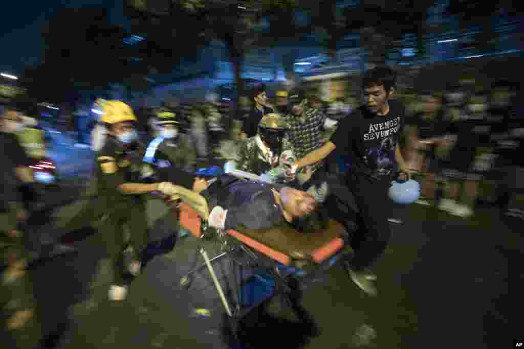 Pro-democracy demonstrators help move a protester with gun-shot injuries during an anti-government rally outside the Parliament in Bangkok, Thailand.