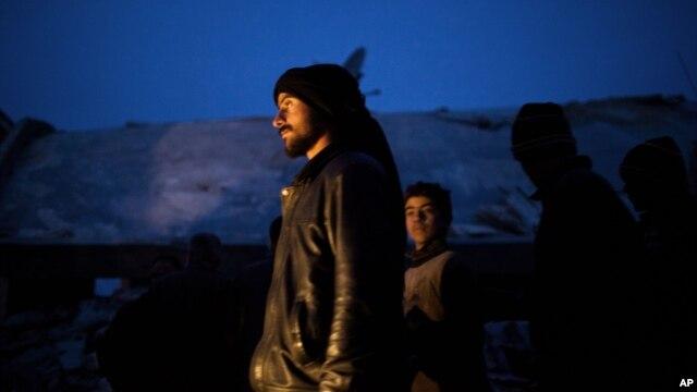 Những người dân Syria đứng gần một khu nhà bị hư hại sau khi bị máy bay của quânội Syria tấn công, 16/12/12