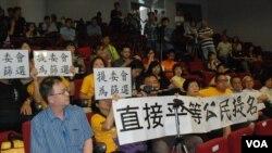 有激進泛民示威者在研討會場內展示爭取公民提名,及提委會等於篩選的標語(美國之音湯惠芸)