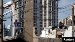 FILE - Workers rest as they demolish an old residential site in the center of Shanghai, September 15, 2013.