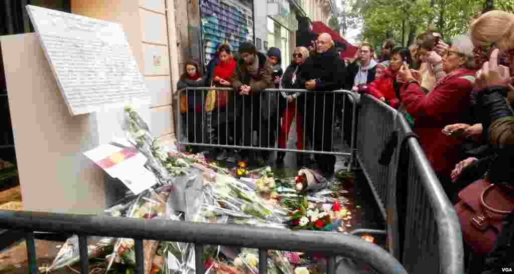 People gather in front of the newly unveiled plaque at the Bataclan concert hall where Islamists killed 90 people last year, in Paris, Nov. 13, 2016. (L. Bryant/VOA)