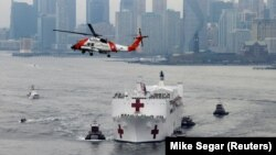 A U.S. Coast Guard helicopter flies above USNS Comfort as it enters New York Harbor during the outbreak of the coronavirus disease (COVID-19) in New York City, U.S., March 30, 2020. (REUTERS/Mike Segar)