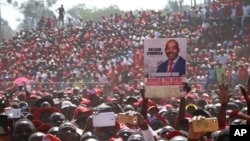 FILE: Movement for Democratic Change (MDC) supporters hold a poster of leader Nelson Chamisa during the party's 19th-anniversary celebrations in Harare, Zimbabwe, Saturday, Oct. 27, 2018.