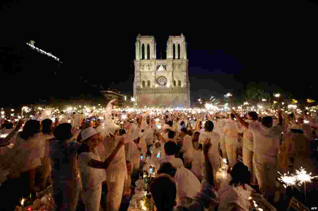 June 16: People celebrate with sparklers as they attend the White Dinner event in front of the Notre Dame Cathedral in Paris. Participants attend the dinner, which takes place at a different place in Paris every year, are required to be dressed in white,