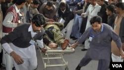 Petugas penyelamat dan warga Pakistan membantu korban luka-luka akibat ledakan bom di provinsi Punjab (15/1).