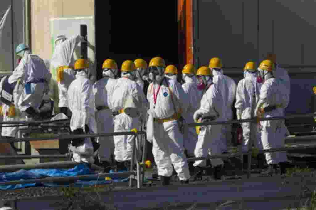 Trabajadores protegidos por sus uniformes y máscaras continúan su trabajo mientras la prensa visita las áreas de la planta de Fukushima, hasta ahora restringidas.