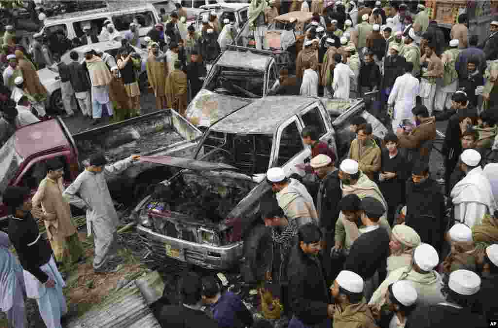 People look at damaged vehicles after a bomb blast in the Pakistani tribal area of Khyber, December 17, 2012.