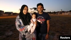 FILE - Ferzanah Essack, 36, a software developer, and her husband Hassan Essack, 37, a software developer, pose for a portrait with their 4-month-old baby Salma on the morning of Ferzanah's first day back to work, in Cape Town, South Africa, Feb. 18, 2019.