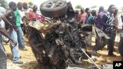 Warga mengerumuni rongsokan mobil yang meledak di lokasi gereja di Yelwa, Bauchi, pada awal bulamn Juni (foto: dok)