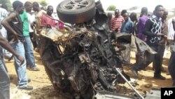 Warga mengerumuni rongsokan mobil yang meledak di lokasi gereja di Yelwa, Bauchi (3/6).
