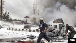Pripadnici službe hitne pomoći na mestu eksplozije na parkingu ispred policijske stanice u prestonici Nigerije, Abudži, 16. jun 2011.