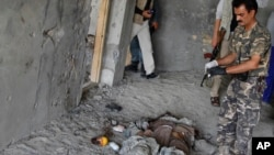 An Afghan security officer stands near the body of an insurgent killed in a battle near Kabul airport, Afghanistan, June, 10, 2013.