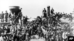 In this May 10, 1869 file photo, railroad officials and employees celebrate the completion of the first railroad transcontinental link in Prementory, Utah. (AP Photo/Union Pacific/Andrew Russell)