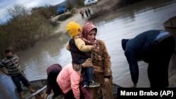 Dalam foto tertanggal 8/12/2012 pengungsi Suriah menyeberangi perbatasan Suriah menuju Turki melalui Sungai Orontes. UNHCR melaporkan perang di Suriah telah memaksa 3 juta orang mengungsi.