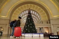 Holiday week train passengers walk by a Christmas tree at Union Station, during the coronavirus disease (COVID-19) pandemic, in Washington, U.S., December 23, 2020.