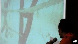 """El jefe de la agencia de Búsqueda y rescate, Bambang Soelistyo, señala una """"A"""" invertida, que identifica la cola del avión de AirAsia."""