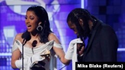"Cardi B accepts the Best Rap Album award for ""Invasion of Privacy"" as her husband Offset kisses her hand. (REUTERS/Mike Blake)"