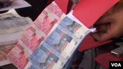 Uang palsu dalam bentuk lembaran yang belum dipotong yang diamankan oleh polisi. (VOA/R. Teja Wulan)