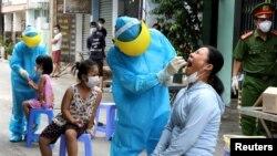 """Nhân viên y tế lấy mẫu xét nghiệm từ người dân trong đợt bùng phát dịch COVID-19 trở lại ở Đà Nẵng hôm 3/8. Thủ tướng Nguyễn Xuân Phúc nói nguy cơ lây nhiễm """"rất cao"""" trong cộng đồng sau khi hàng chục nghìn người trở về các tỉnh thành từ Đà Nẵng."""