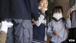 Dua orang anak menyaksikan ayahnya sedang dideteksi oleh petugas apakah terkena radiasi di Fukushima, Jepang (29/3).