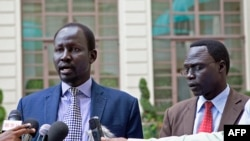 Lul Ruai Koang (L), the military spokesman for opposition forces in South Sudan, and James Gatdet Dak, spokesman for opposition leader Riek Machar, speak to reporters in Addis Ababa on May 9, 2014.