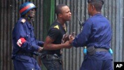 An anti government protestor, center, is arrested by FILE - Congo riot troops, during a protest against a new law that could delay elections to be held in 2016, in the city of Kinshasa, Democratic Republic of Congo, Jan. 19, 2015.