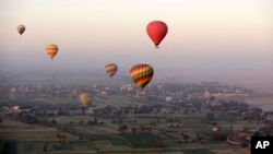 FILE - Hot air balloons fly over the west bank of the Nile River in Luxor, Egypt, April 1, 2016.