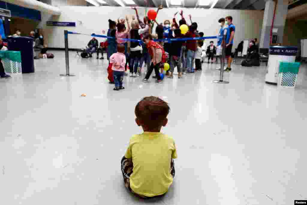 A child sits on the floor at Fiumicino Airport, as Afghan evacuees arrive in Italy following their journey from Kabul, in Rome, Italy.