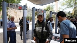 An Israeli border police officer asks to check the identity of a Palestinian man next to newly installed metal detectors at an entrance to the compound known to Muslims as Noble Sanctuary and to Jews as Temple Mount in Jerusalem's Old City, July 16, 2017.