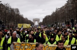 FILE - Yellow Vests protesters march on the Champs Elysees avenue in Paris. France's yellow vest protesters remain a force to be reckoned with five months after their movement started.