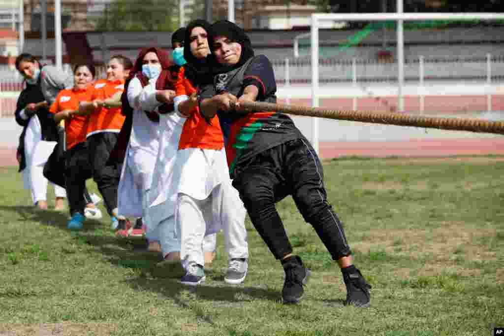 Women participants in a tug of war contest on the International Women's Day celebrations in Peshawar, Pakistan.