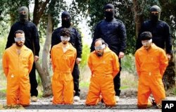 This undated image released by a militant website, which has been verified and is consistent with other AP reporting, shows members of the Islamic State group as they prepare to kill men who were allegedly spying for the U.S.-led coalition.