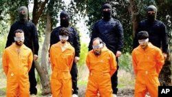 This undated image released by a militant website, which has been verified and is consistent with other AP reporting, shows members of the Islamic State group as they prepare to kill men who were allegedly spying for the U.S.-led coalition in the province of Salah al-Din, Iraq.