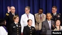 Tại Tòa Bạch Ốc hôm 11/2/2015, Tổng thống Obama nhắc tới một thành viên của quân đội Hoa Kỳ tham gia nỗ lực đối phó dịch Ebola ở Tây Phi (giơ tay đứng hàng sau) trong bài phát biểu về những tiến bộ đạt được trong quá trình này.