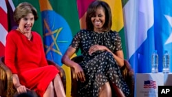 "U.S. first lady Michelle Obama, right, and former U.S. first lady Laura Bush laugh as they participate in the African First Ladies Summit: ""Investing in Women: Strengthening Africa,"" hosted by the George W. Bush Institute, July 2, 2013, in Dar es Salaam,"