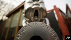 "FILE - A sculpture is displayed with the phrase ""Made in China,"" at the 798 Art District in Beijing, China, Nov. 21, 2012."