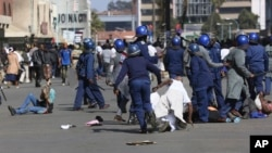 FILE: Riot police arrest and forcibly apprehend protestors during protests in Harare, Friday, Aug, 16, 2019.
