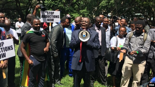 """Former Zimbabwean Prime Minister Morgan Tsvangirai addresses activists in Harare protesting the disappearance a year ago of Itai Dzamara, March 9, 2016. He said the case represented """"the unacceptable face"""" of Robert Mugabe's government. (S. Mhofu/VOA)"""