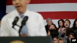 Un inmigrante surcoreano grita en el fondo al presidente Obama, pidiendo que pare las deportaciones.
