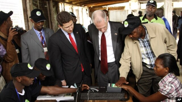 Independent Electoral and Boundaries Commission's, IEBC, U.S. Ambassador to Kenya, Robert F. Godec, second right and British High Commissioner to Kenya, Christian Turner, second left, inside the voter registration centre in Thika Nairobi Kenya, Dec. 15, 2
