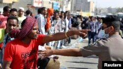 An Ethiopian worker argues with a member of the Saudi security forces.