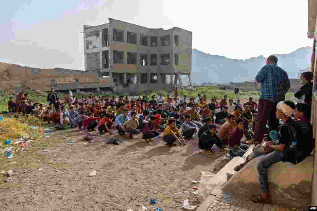 Yemeni students attend class in their destroyed school compound on the first day of the new academic year in the country's third-city of Taez.