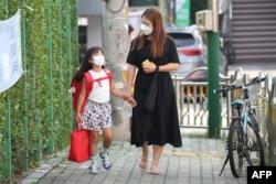 Seorang ibu mengantar anaknya berangkat ke sekolah di Seoul, Korea Selatan, 25 Agustus 2020.