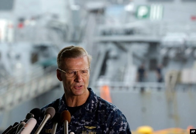 Vice Adm. Joseph Aucoin, commander of the U.S. 7th Fleet, speaks during a press conference, with the damaged USS Fitzgerald in the background at the U.S. Naval base in Yokosuka, southwest of Tokyo, June 18, 2017.