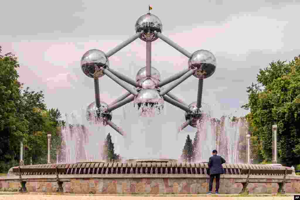 A tourist looks at a fountain at the Atomium in Brussels, Belgium.